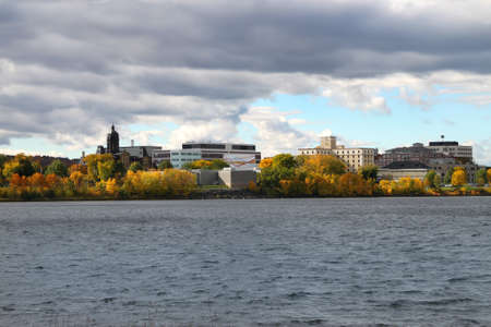 View  Fredericton, New Brunswick, along the Saint John River, Canada showing downtown buildings and  Fall foliage