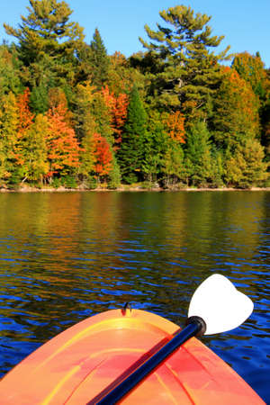 maritimes: Kayak on the river with colorful trees in the background in early Autumn season in New Brunswick, The Maritimes in Canada. Focus on front of kayak
