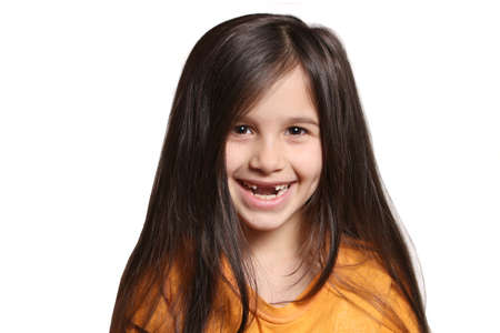 seven year old: Little seven year old, happy girl shows big smile showing missing top front teeth on a white background