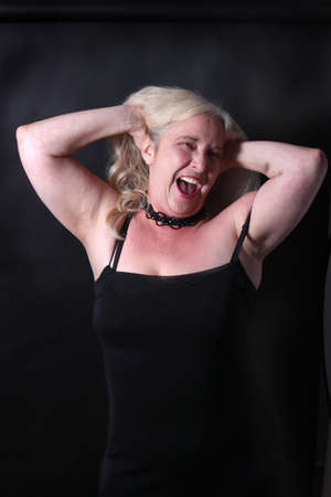 fifties: Pretty, confident, middle aged woman in her fifties having fun on a dark background