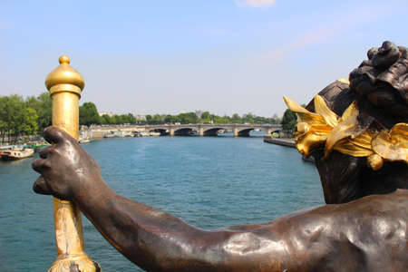alexandre: Looking over the shoulder of a nymph statue made with hammered copper that overlooks the Seine on Pont Alexandre III