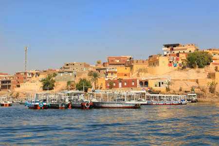 docked: Wooden boats docked along the Nile River in Egypt, North Africa with houses in the background
