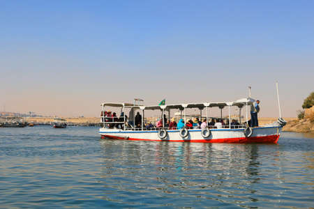 water transportation: ASWAN, EGYPT - FEBRUARY 1, 2016: Wooden boats carrying passengers along the Nile River in Egypt, North Africa