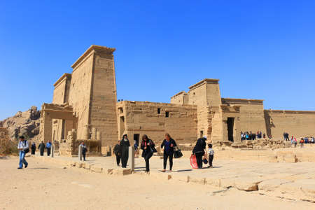 cult: ASWAN, EGYPT - FEBRUARY 1, 2016: Tourists visiting the Graeco-Roman Temple of Philae  dedicated to the cult of Isis in Egypt