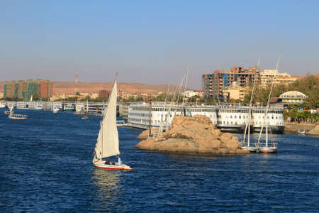 nile river: Boats docked and fellucas sailing along the shore of the Nile River at Aswan, Egypt Stock Photo