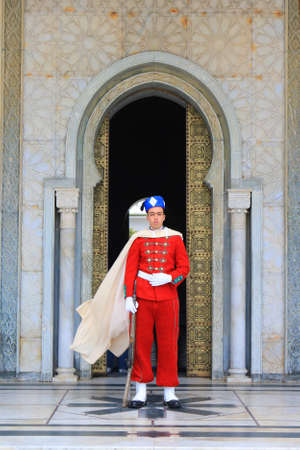 royals: RABAT. MOROCCO - FEBRUARY 20, 2016: Royal guard at entrance of the Mausoleum of Mohammed V wearing traditional attire of red in the winter.