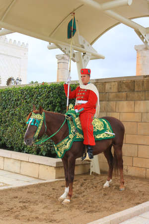 mohammed: RABAT. MOROCCO - FEBRUARY 20, 2016: Mounted  Royal guard at entrance of the Mausoleum of Mohammed V on horseback wearing traditional attire of red in the winter. Editorial