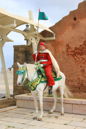 mounted: RABAT. MOROCCO - FEBRUARY 20, 2016: Mounted  Royal guard at entrance of the Mausoleum of Mohammed V on horseback wearing traditional attire of red in the winter. Editorial