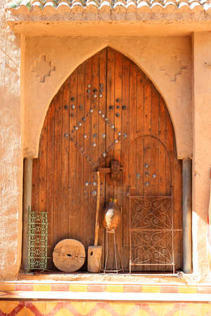 adobe: Wooden door of an adobe house along a street in Rissani, Morocco