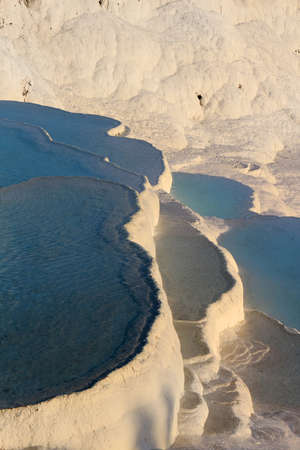 White travertine terraces made from the hots springs leaving deposits of calcium  at Pamukkale or Cotton Castle