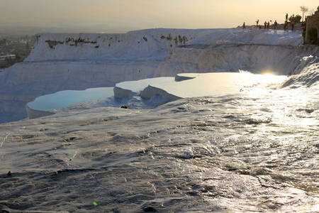 hots: White travertine terraces made from the hots springs leaving deposits of calcium  at Pamukkale or Cotton Castle next to  Hierapolis, Turkey in the evening