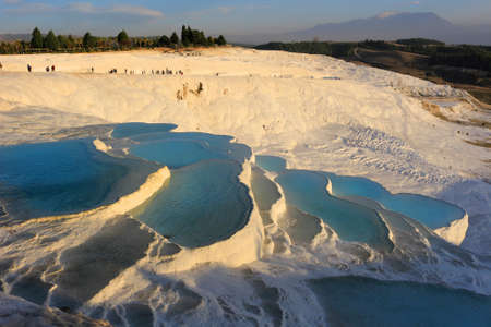 carbonate: White travertine terraces made from the hots springs leaving deposits of calcium  at Pamukkale or Cotton Castle