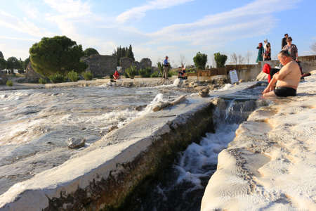 hots: PAMUKKALE, TURKY - FEBRUARY 18, 2016: People enjoying the thermal waters of the White travertine terraces made from the hots springs leaving deposits of calcium  at Pamukkale or Cotton Castle next to  Hierapolis, Turkey in the evening Editorial