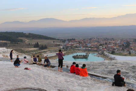 hots: PAMUKKALE, TURKEY - FEBRUARY 18, 2016: People enjoying the views and the thermal stream on the White travertine terraces made from the hots springs leaving deposits of calcium  at Pamukkale or Cotton Castle next to  Hierapolis, Turkey in the evening Editorial