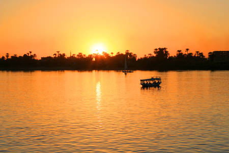 nile river: Golden sunset along the Nile River in Egypt with boat making its crossing