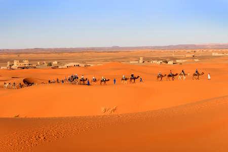 erg: ERG CHEGGI, MOROCCO - FEBRUARY 28, 2016: People riding on a caravan of camels towards the dunes of the Sahara Desert at Erg Cheggi, Morocco at sunset Editorial