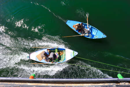 nile river: NILE RIVER, EGYPT - FEBRUARY 3, 2016: Men in a row boat tied to the side of a Nile River Cruise ship trying to sell scarves to the passengers in Egypt