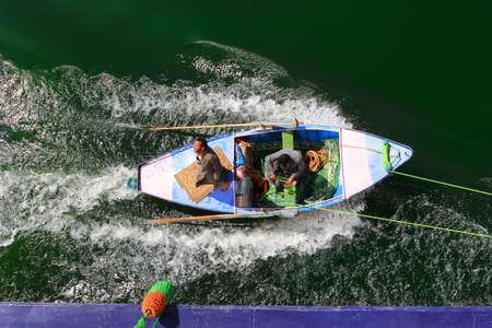 foulards: Fiume Nilo, Egitto - 3 febbraio 2016: Uomini in una barca a remi legata al lato di una nave da crociera Nilo cercando di vendere sciarpe ai passeggeri in Egitto