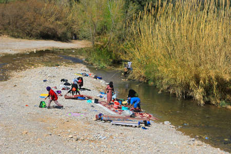 headress: MOROCCO, AFRICA - MARCH 2, 2016: Women washing their clothes on a small river in Morocco, Africa