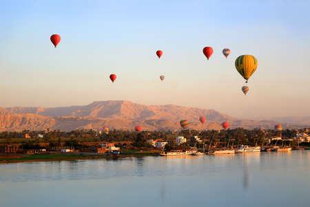 日の出ルクソールのナイル川に浮かぶ多くの熱気球