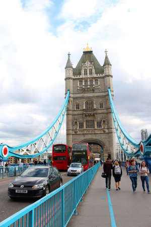 LONDON, ENGLAND - JUNE 17, 2015: Traffic and pedestrians crossing under the towers of the Historic London Bridge over the River Thames  in London England Redactioneel