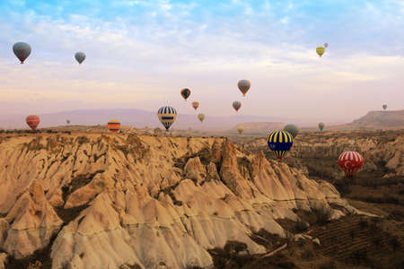 ballooning: CAPPACOCIA, TURKEY - FEB. 15, 2016: Hot air balloon  in the  early morning during sunrise over the rock formations of Cappadocia, Turkey