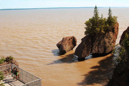 nb: Unidentidies Backpackers on a platform  viewing  Hopewell Rocks in the Bay of Fundy, New Brunswick, Canada in the muddy water at high tide Stock Photo