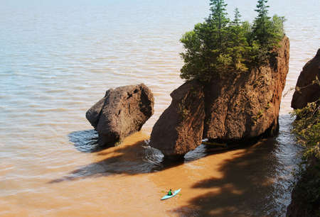 tides: Kayaker at Hopewell Rocks in the Bay of Fundy, New Brunswick, Canada in the muddy water at high tide