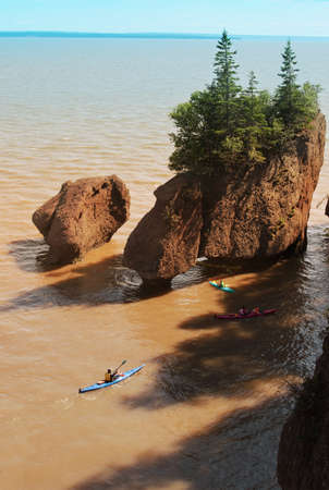 nb: Kayakers at Hopewell Rocks in the Bay of Fundy, New Brunswick, Canada in the muddy water at high tide Stock Photo