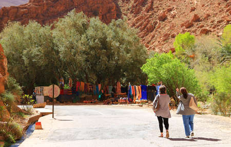 canyon walls: Todra Canyon, Morocoo - February 27, 2016: Women walk along the road next to Steep canyon walls in colorful Todra Gorge in Morocco Africa showing shop with colorful cothing for sale Editorial