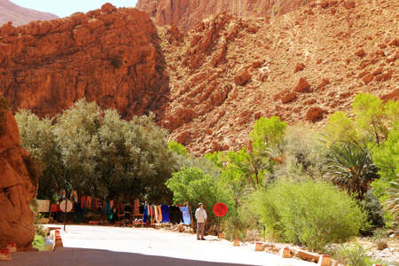 canyon walls: Todra Canyon, Morocoo - February 27, 2016: Steep canyon walls in colorful Todra Gorge in Morocco Africa showing shop with colorful cothing for sale
