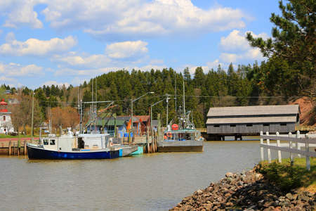 maritimes: Boat and covered Bridge in St. Martins, New Brunswick during High Tide on the Bay of Fundy, Canada