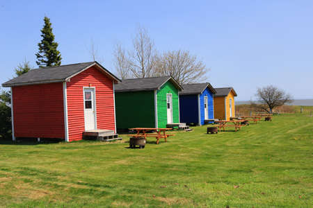 Colorful one room shacks or cabins with picnic tables and fire pits near the ocean in St. Martins New Brunswick, Canada Stok Fotoğraf