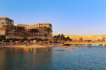 hurghada: Hurghada, Egypt - Feb 7, 2016: People enjoying the beach area with sun shades and lounging chairs at a resort on the Red Sea in Hurghada, Egypt