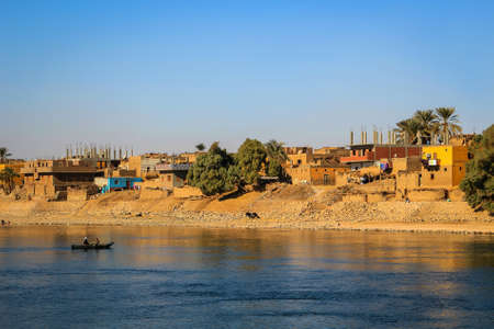 abodes: Nile River, Egypt, - February 3, 2016: People on a boat with Village along the shore of the Nile River in Egypt, Africa at sunset Editorial