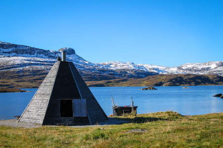 Lake with snow covered mountains and triangular  shack for  firepit and warmth in cold weather  in the Telemark region Norway, Scandinavia
