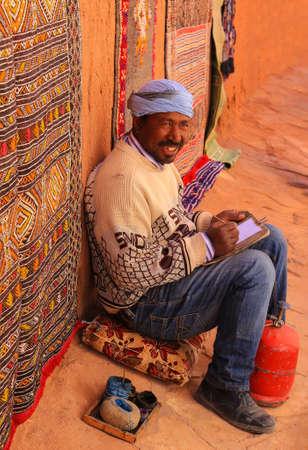 Ait Benhaddou, Marokko - 3. März 2016: Mann sitzt aus den Grund mit den Künstlerversorgungen, die in ummauerter Stadt von Ait Benhaddou, Marokko, Afrika skizzieren und lächeln Standard-Bild - 71283021