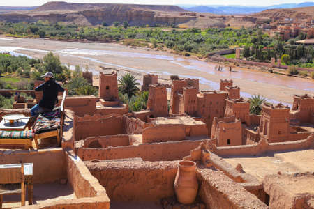 Ait Benhaddou, Morocco - March 3, 2016: Man sits on the rooftop cafe overlooking the valley in Ait Benhaddou, Morocco, Africa