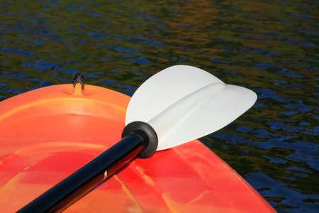 Heldere oranje kajak en paddle op het water met kleurrijke reflecties
