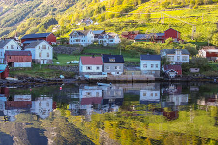 waterfront property: Colorful Houses in a waterfront village with nature along the shore of Sognefjord, Norway, Scandinavia