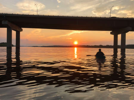 Kayaker on the Saint John River at sunset near downtown Fredericton, New Brunswick in The Maritimes or Atlantic Canada