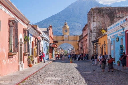 Antigua, Guatemala - March 4, 2017: Cobblestone street with Colorful landmark Santa Catalina Arch dating to the 1600s & topped by a clock built in the 1800s in Antigua, Guatemala with volcanic mountain in the background