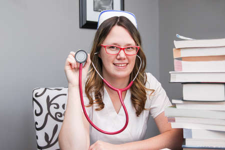 Young smiling  female nurse portrait wearing white scrubs, cap holding a stethoscope ready to check your heartbeat  with nursing textbooks on the table Imagens