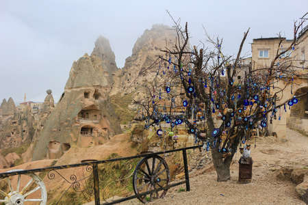 Glass blue Nazars, charms to ward off the evil eye hanging off the branches of a tree in the rain in Cappadocia Turkey