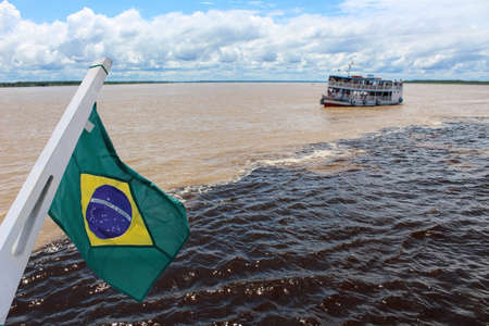 Meeting of the Waters of Rio Negro and the Amazon River or Rio Solimoes near Manaus, Amazonas, Brazil in South America with waving Brazil flag Banco de Imagens