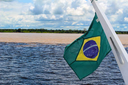 Meeting of the Waters of Rio Negro and the Amazon River or Rio Solimoes near Manaus, Amazonas, Brazil in South America with waving Brazil flag Reklamní fotografie