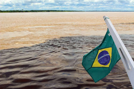 Meeting of the Waters of Rio Negro and the Amazon River or Rio Solimoes near Manaus, Amazonas, Brazil in South America with waving flag of Brazil Reklamní fotografie