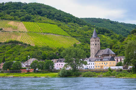 Small town with church along the shore of the Rhine river in Germany, Europe