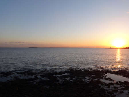 Photo of sunset over the sea, filmed from the coast Stock Photo
