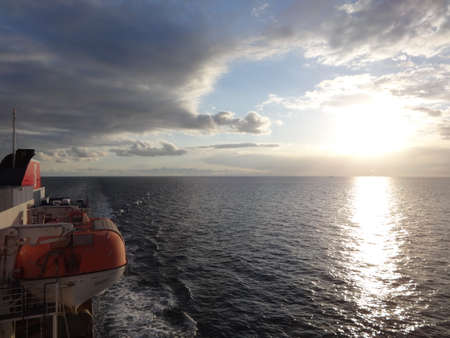Photo of sunset over the sea, flmed from the ship Stock Photo